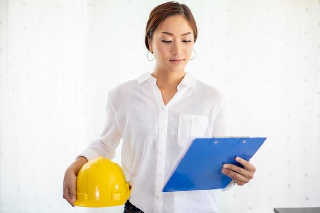Asiatiques ingénierie inspectant et travaillant et tenant des plans au bureau. elle sourit heureuse pour le travail
