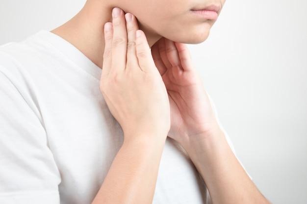 Les asiatiques ont mal à la gorge en utilisant deux mains pour toucher le cou. isolé sur blanc
