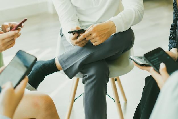 Les asiatiques sont assis ensemble en cercle, chacun utilisant un téléphone central, personne ne faisant attention à personne.