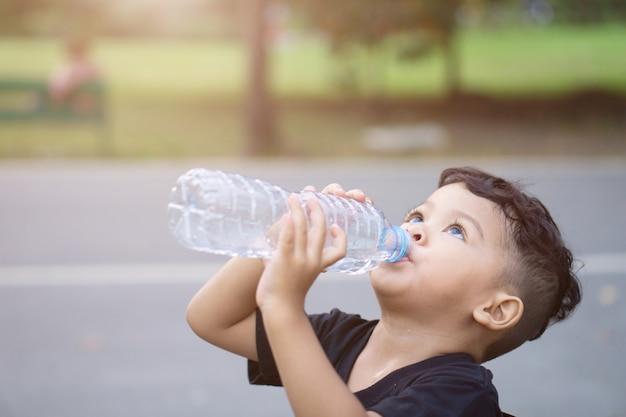 Asiatiques thaïlandais enfants boivent de l'eau dans le parc