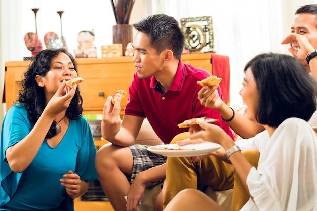 Asiatiques en train de manger une pizza à la fête