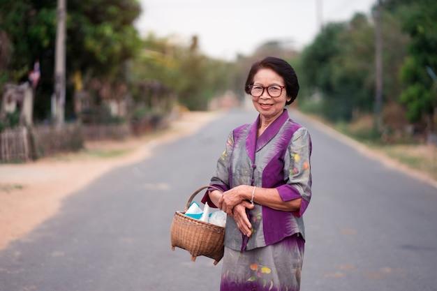 Asiatiques vieilles femmes tenant un panier de bambou dans la campagne.