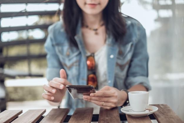 Asie femme assise dans le café et à l'aide de téléphone portable