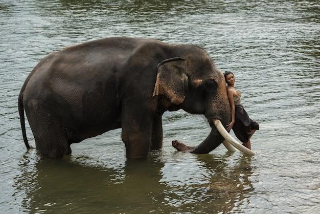 Asie femme en costume de style traditionnel avec éléphant en rivière