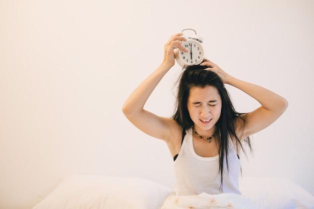 Asie femme endormie ne veut pas se lever à 6h00 du matin par réveil.