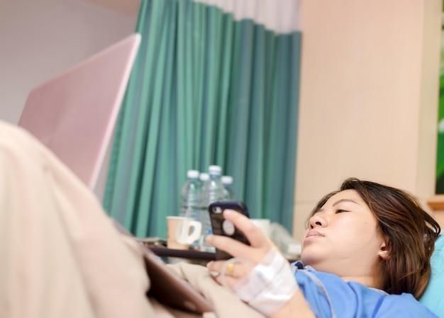 Asie femme patiente travaillant avec un ordinateur portable au cours de l'hôpital
