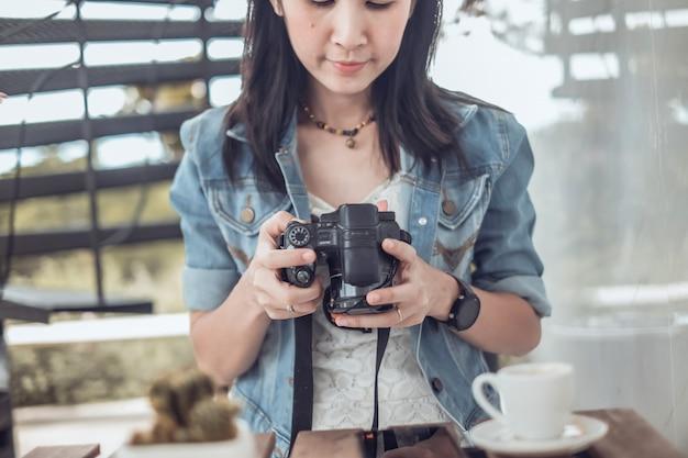 Asie, femme, voyageur, boire café, regarder, photo, sur, appareil photo