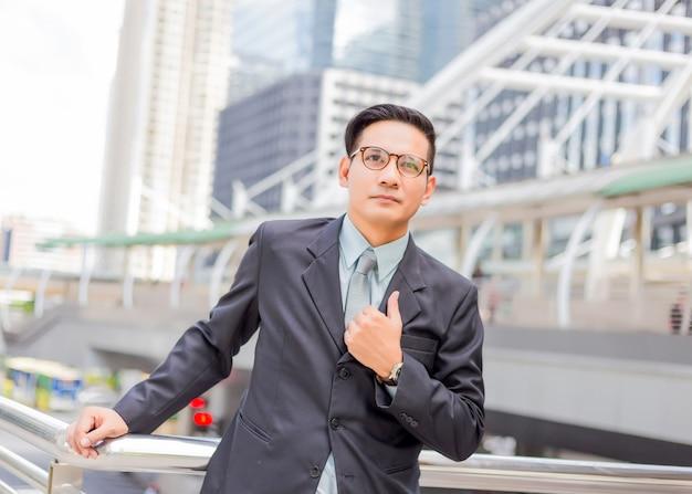 Asie jeune homme d'affaires en face de l'immeuble moderne au centre-ville. concept de jeunes hommes d'affaires
