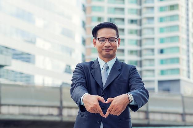 Asie jeune homme d'affaires faisant un coeur avec ses mains sur blanc