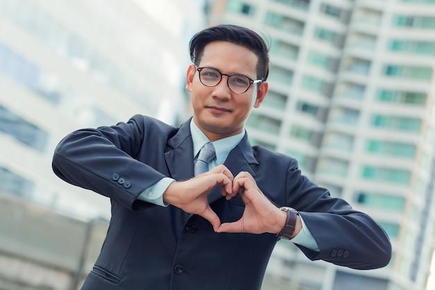 Asie jeune homme d'affaires faisant un coeur avec ses mains sur fond blanc, j'adore les affaires