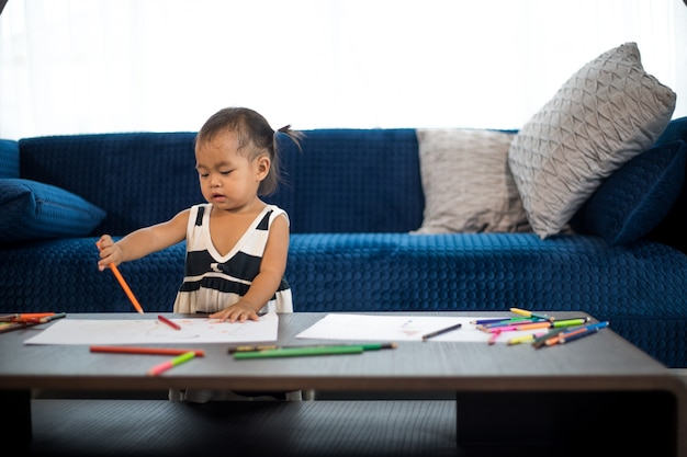 Asie petite fille dessinant une famille sur une grande feuille de papier blanc