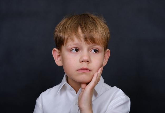 Aspect européen de garçon triste avec des larmes dans ses yeux. isoler sur un noir