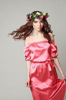 Aspect romantique doux de la jeune fille avec une couronne de roses sur la tête et une robe rose. joyeuse femme de printemps jolly. dame d'été en robe longue rose