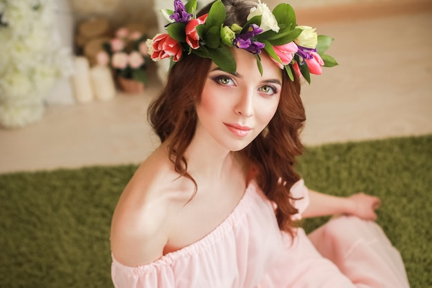 Aspect romantique doux de la jeune fille avec une couronne de roses sur la tête et une robe rose.