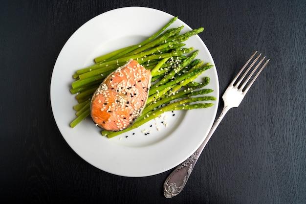 Asperges au saumon sur une assiette blanche. sur un fond noir