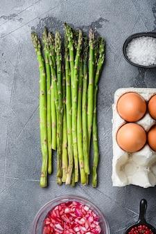 Asperges aux œufs et ingrédients de vinaigrette française avec moutarde de dijon, oignon haché dans du vinaigre rouge à l'estragon sur fond texturé gris, vue de dessus.