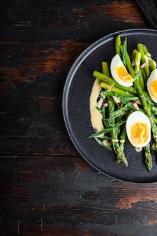 Asperges aux œufs et vinaigrette française à la moutarde de dijon, oignon haché au vinaigre rouge taragon sur la vieille table en bois sombre, vue de dessus avec un espace pour le texte.