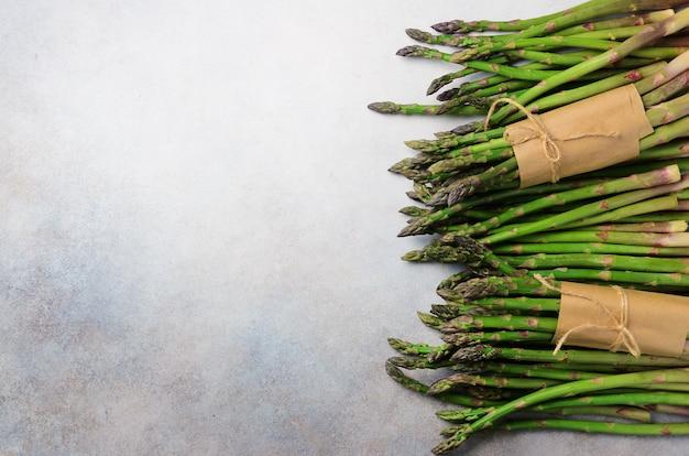 Asperges fraîches vertes sur fond gris. vue de dessus. concept de restauration cru, végétalien, végétarien et propre.