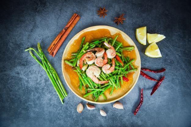 Asperges frites crevettes crevettes cuisson des aliments sur une assiette en bois et des épices aux herbes herbes tas d'asperges fraîches sur la table à manger