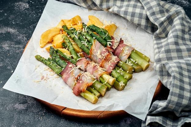 Asperges grillées avec bacon, parmesan et pommes de terre sur parchemin blanc. surface sombre