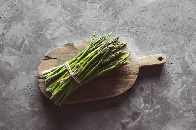 Asperges sur une planche à découper. une alimentation saine, la santé sur un mur de béton.