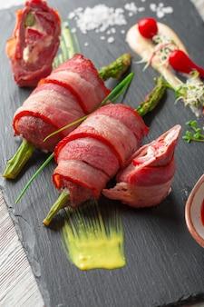 Asperges roulées au bacon grillé servies avec une sauce sur une assiette noire