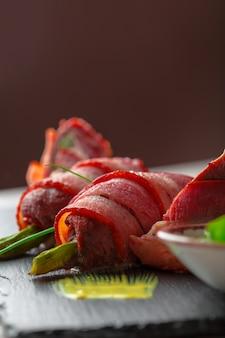 Asperges roulées dans du bacon grillé servies avec sauce sur plaque noire