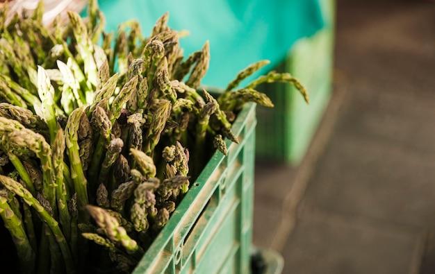 Asperges vertes biologiques dans une caisse en plastique à vendre sur un étal de marché