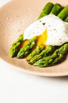 Asperges vertes bouillies avec œuf poché, sel et épices