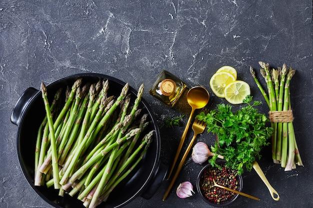 Asperges vertes fraîches dans un plat de cuisson noir avec couverts dorés, tranches de citron, grains de poivre et bouteille d'huile d'olive sur la table en béton gris