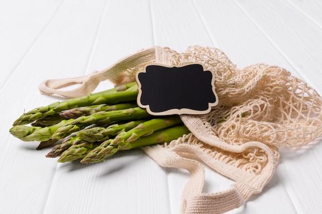 Asperges vertes fraîches dans un sac à provisions sur une table en bois blanc