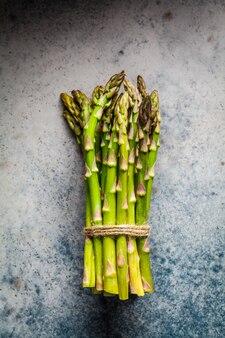 Asperges vertes fraîches sur fond gris, vue de dessus. concept de nourriture végétalienne saine.