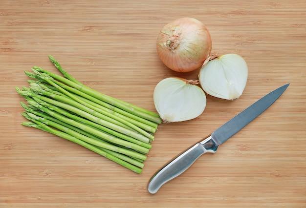 Asperges vertes fraîches et oignons avec un couteau tranchant sur fond de planche de bois.