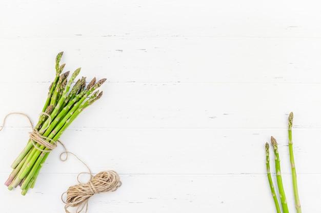 Asperges vertes fraîches sur une surface en bois blanche