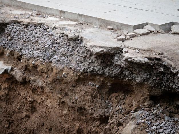 Asphalte cassé et une fosse, travaux routiers. réparation de la route, creuser la chaussée avec de l'asphalte et des pavés.