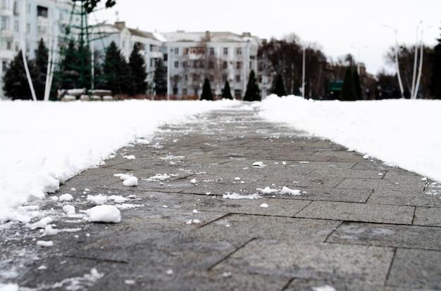 Asphalte d'hiver en macro. le chemin à travers la neige. le trottoir est l'hiver.