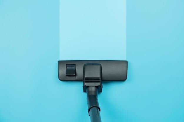 Aspirateur sur le fond de plancher bleu.