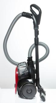 Aspirateur noir et rouge avec récipient sans tuyaux sur fond blanc