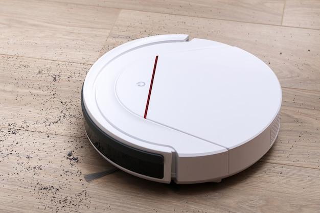Un aspirateur robot blanc élimine les débris sur le sol du stratifié.