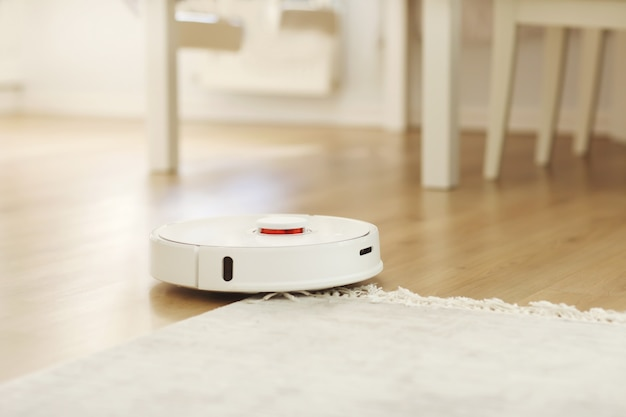 L'aspirateur robot effectue un nettoyage automatique de l'appartement à un certain moment. aspirateur robot blanc. nettoyage à domicile. maison intelligente. mise au point sélective