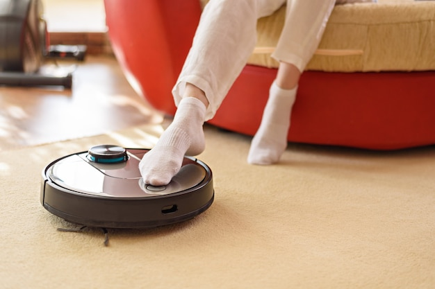 Aspirateur robotique et jambes sur tapis, appareils intelligents dans le concept de maison, concept de mode de vie paresseux et confortable, repos