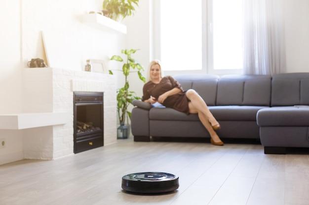 Aspirateur robotique nettoyant la pièce pendant que la femme se repose sur le canapé