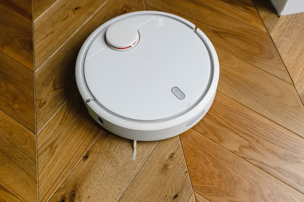 Aspirateur robotique sur plancher en bois stratifié technologie de nettoyage intelligente.