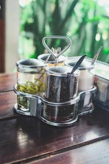 Assaisonnement à la manière des nouilles thaïlandaises: sucre, piment au vinaigre, poudre de piment rouge sur la table.