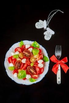 Assaisonnement de tomates en tranches avec salade de mozzarella, basilic en assiette sur fond noir. vue de dessus.