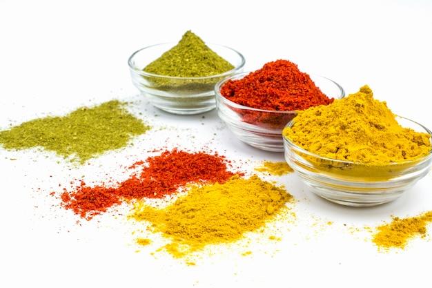Assaisonnements parfumés dans des bols en verre : curcuma, mélange d'herbes aromatiques, piment rouge isolé sur fond blanc.