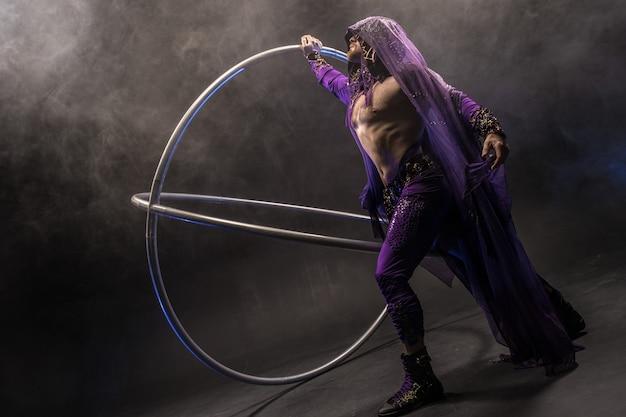 Assassin de personnage de conte de fées dans un manteau violet avec une capuche avec deux grands cerceaux de roue cyr