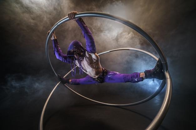 Assassin personnage de conte de fées est assis sur le grand écart dans un manteau violet avec une capuche avec deux grands cerceaux de roue cyr