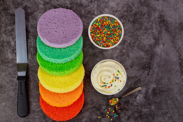 Assemblage du gâteau en couches arc-en-ciel avec de la crème blanche et des pépites.