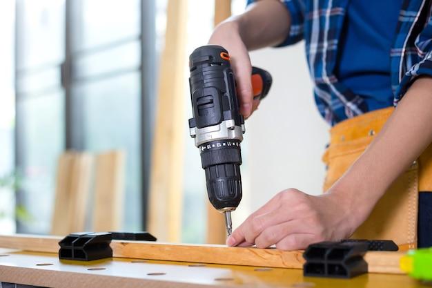 Assembler des meubles. homme tenant une perceuse-visseuse électrique assemblant des meubles, artisan avec une perceuse dans un tournevis électrique